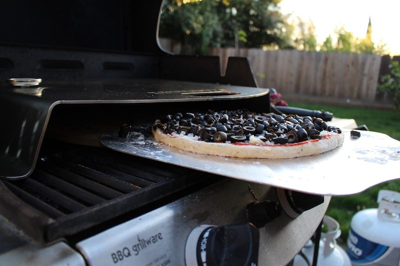 putting homemade olive pizza into gas grill with kettlepizza and pizza stone