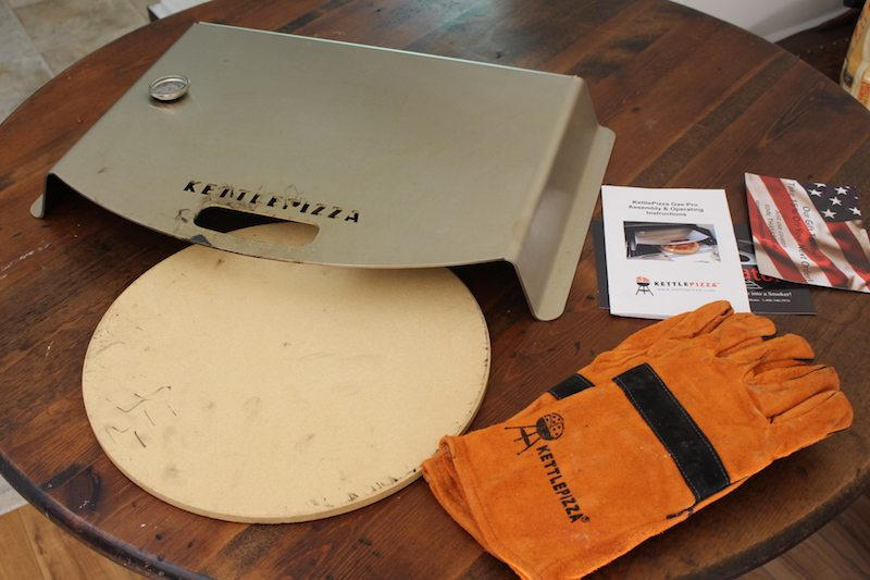 kettlepizza gas with pizza stone and barbecue heat resistant gloves on wooden table