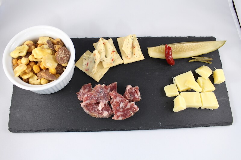 white background with black slate cheese platter. on top is cheese spread, crackers, salami, and fried fava bean mix