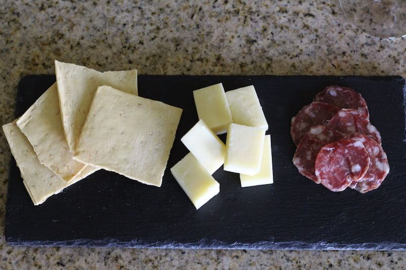 wheat crackers, white cheese, and salami on a stone plate for serving