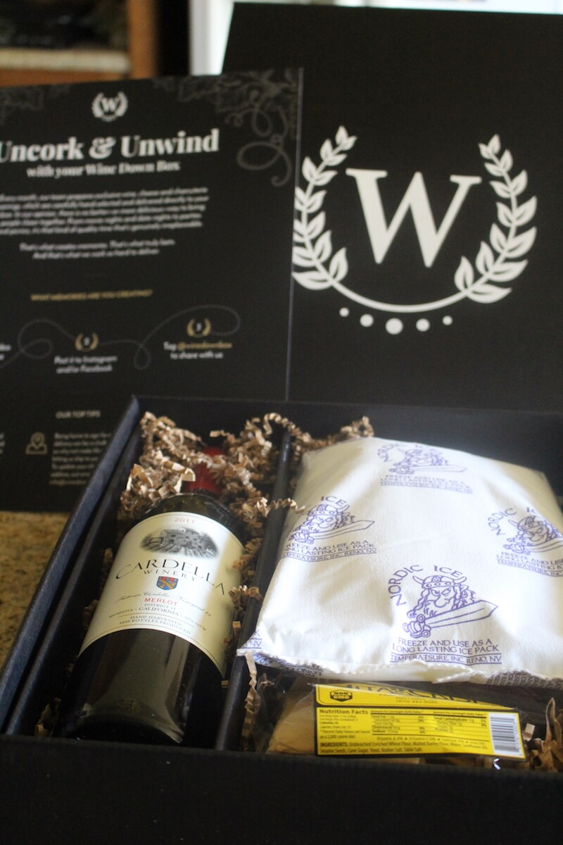 wine down box package unopened with bottle of red wine, crackers, charcuterie, cheese, and ice pack