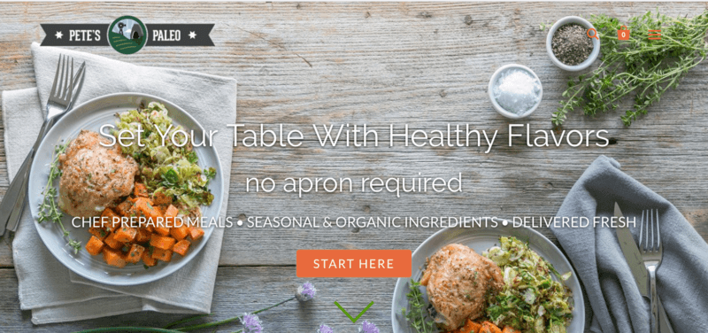 screenshot of pete's paleo meal service showing two fully prepared meals that include chicken, carrots and a salad on a wooden table