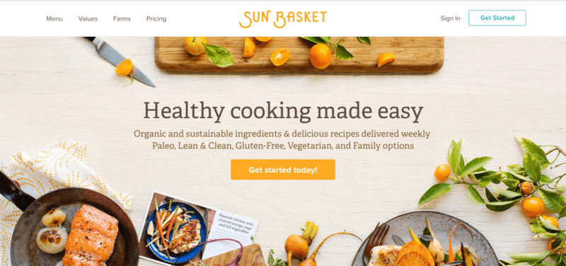 sun basket gluten free meal kit website screenshot showing a salmon meal, a chicken meal and various oranges on a white background.