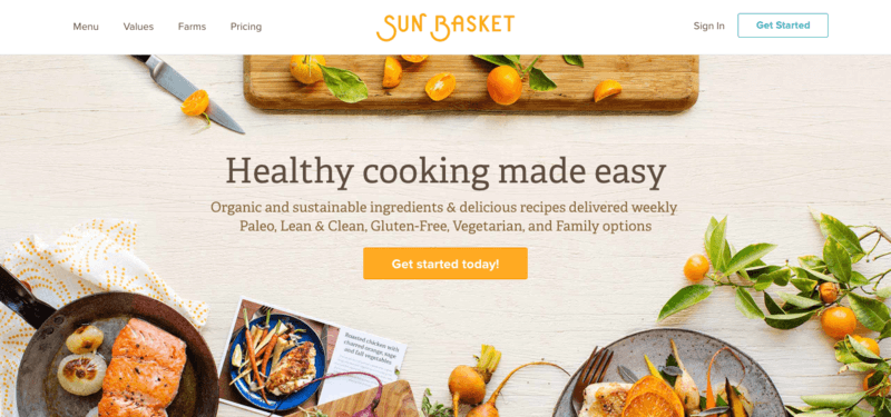 sun basket meals website screenshot showing various oranges, salmon in a pan and cooked chicken on a light-colored wood background.
