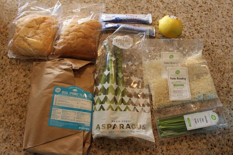 fresh ingredients sitting on counter including ciabatta rolls, lemon, sour cream, panko breading tilapia, and asparagus