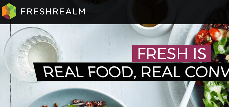 fresh realm meals website screenshot showing a table with a glass of water, along with parts of a salad and a quinoa dish
