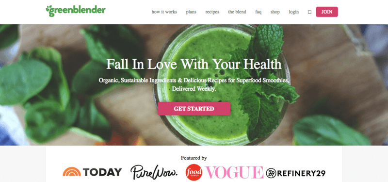 green blender website screenshot showing a top down view of a green smoothie in focus with an out of focus bread board and greens below