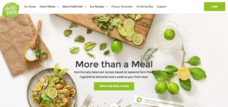 Screenshot from the HelloFresh Website showing a white table, limes and a prepared dinner that includes chicken, rice and various other components.