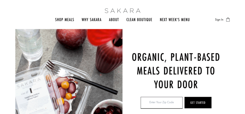 Sakara website screenshot showing a fruit salad on a gray table, along with water.