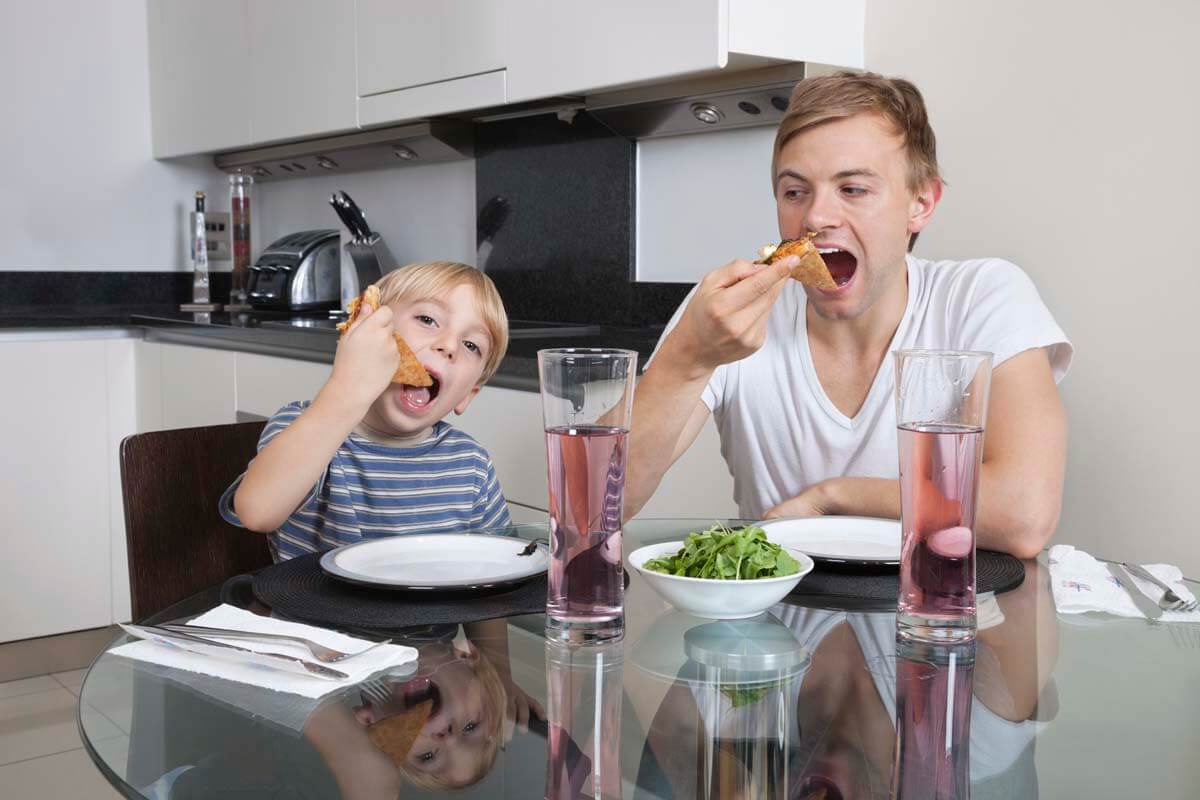 Father and son eating pizza at breakfast table