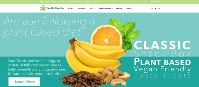 Healthy Surprise website screenshot showing cashews, bananas, saltanas, an orange and mint, near text that provides many details about the snack box and a plant-based diet.