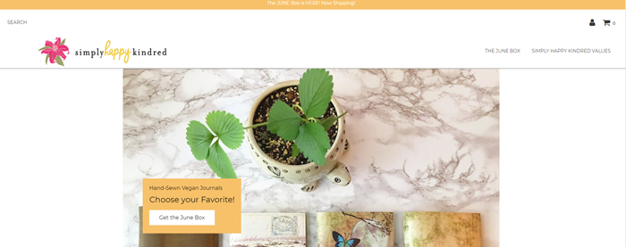 Simply Happy Kindred website screenshot showing a marble table with a plant and some notebooks.