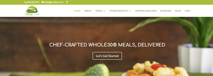 True Fare website screenshot showing wan image of a dinner on a table, along with a pot plant in the background.