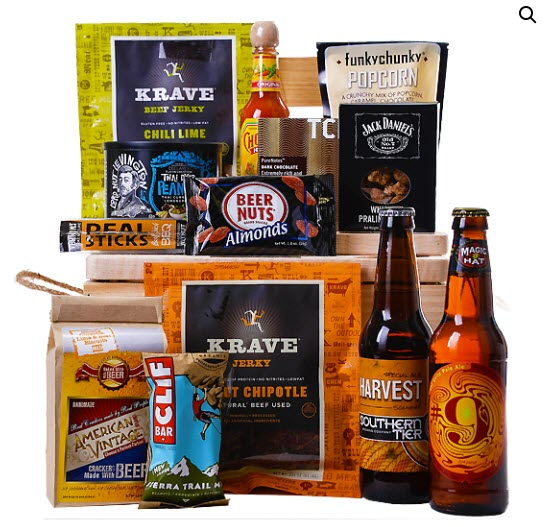 A wide selection of snacks resting on top of a crate, with more in front of it, along with 2 bottles of beer.
