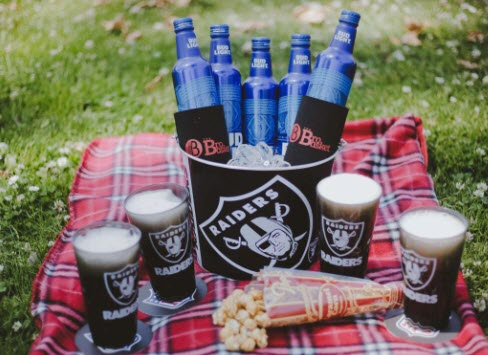 A Raiders bucket on a picnic blanket containing 5 Bud Light bottles. On the blanket are 4 filled Raiders glasses on coasters and a spilled container of popcorn.