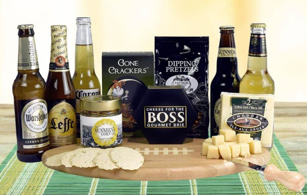 A selection of beers and snacks surrounding a football cutting board. There are also some snacks on the board itself.