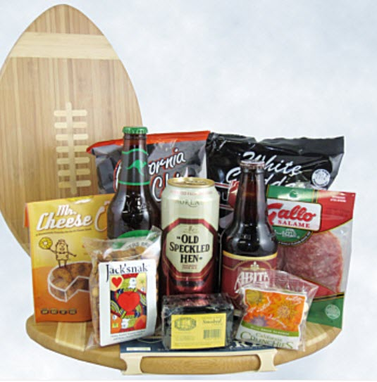 A football shaped cutting board with 3 beers and a selection of snacks on top.