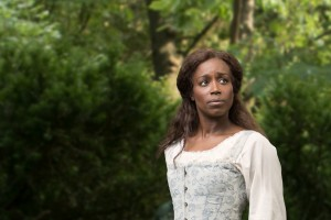A young enslaved woman stands in a grove of trees wearing a 1700s-era costume.