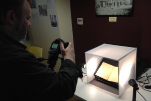 Photographer aims a camera at a shadowbox which is lighted to show an open diary page.