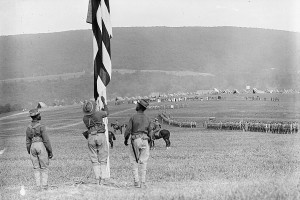 A Civil War-era battlefield photograph showing uniformed soldiers walking toward distant hills. One soldier carries a Union flag.