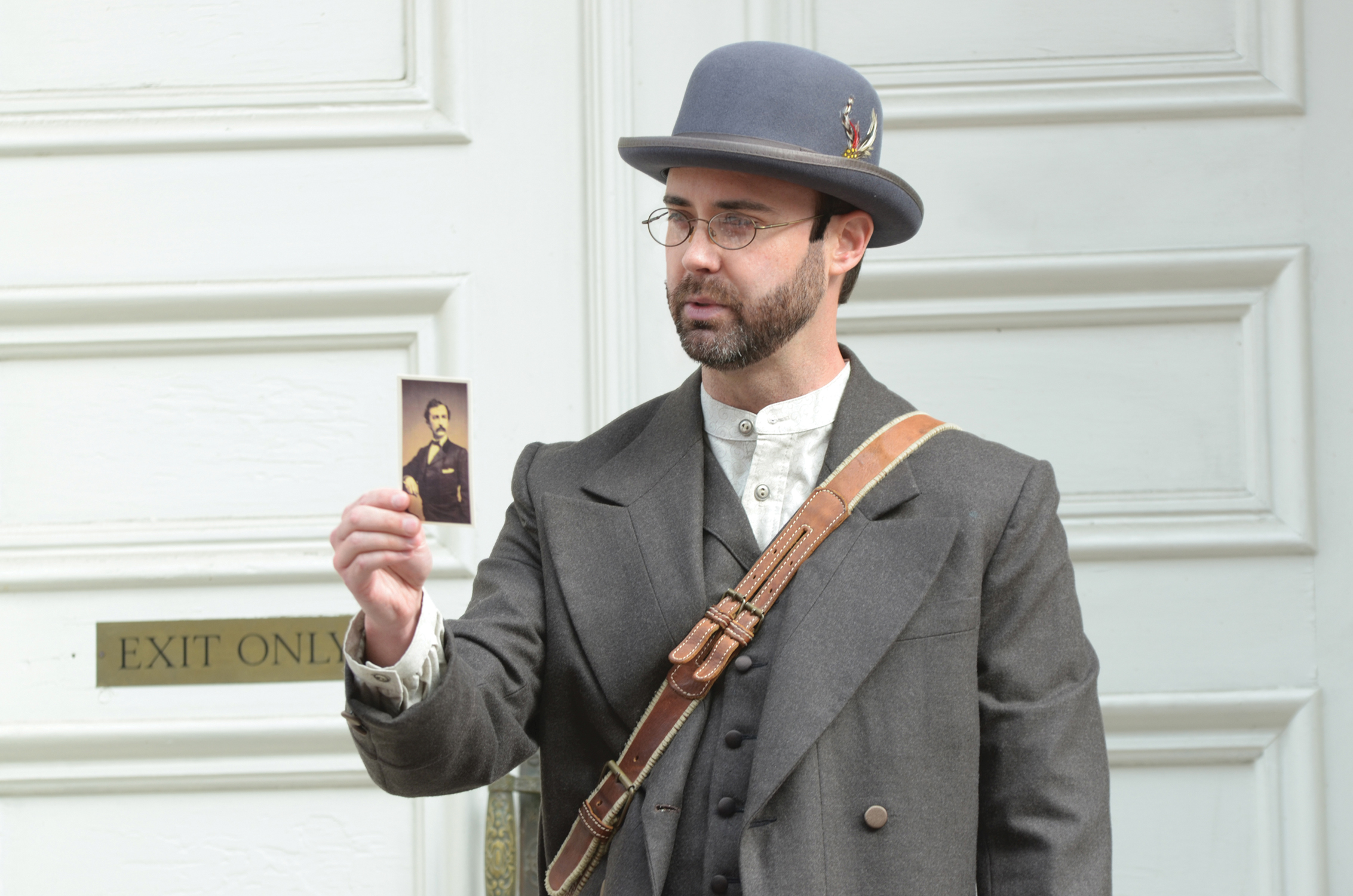 Actor William Diggle, dressed as Detective James McDevitt, holds a photo of assassin John Wilkes Booth as he leads a tour outside of Ford's Theatre.