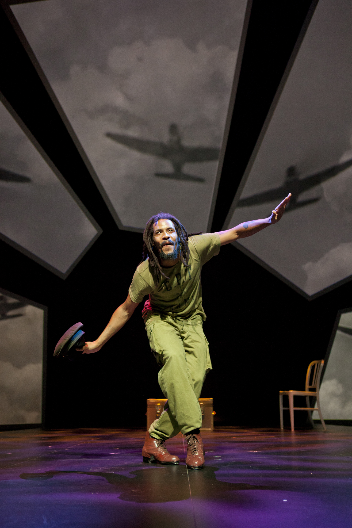 "Image of dancer Omar Edward on the set of the play ""Fly"" at Ford's. Edwards wears a green military jumpsuit and has his hair in dreadlocks. Behind him are multiple projections of flying Tuskegee aircraft. Edward is posed on one leg with his arms outstretched as if he is flying."