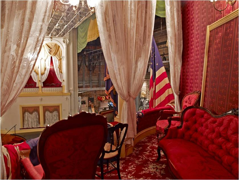 Photo from the balcony hallway of Ford's Theatre looking onto the stage from the vantage of the Presidential Box. Images shows the reproduction red rocking chair and other items that surrounded President Lincoln the night of the assassination/