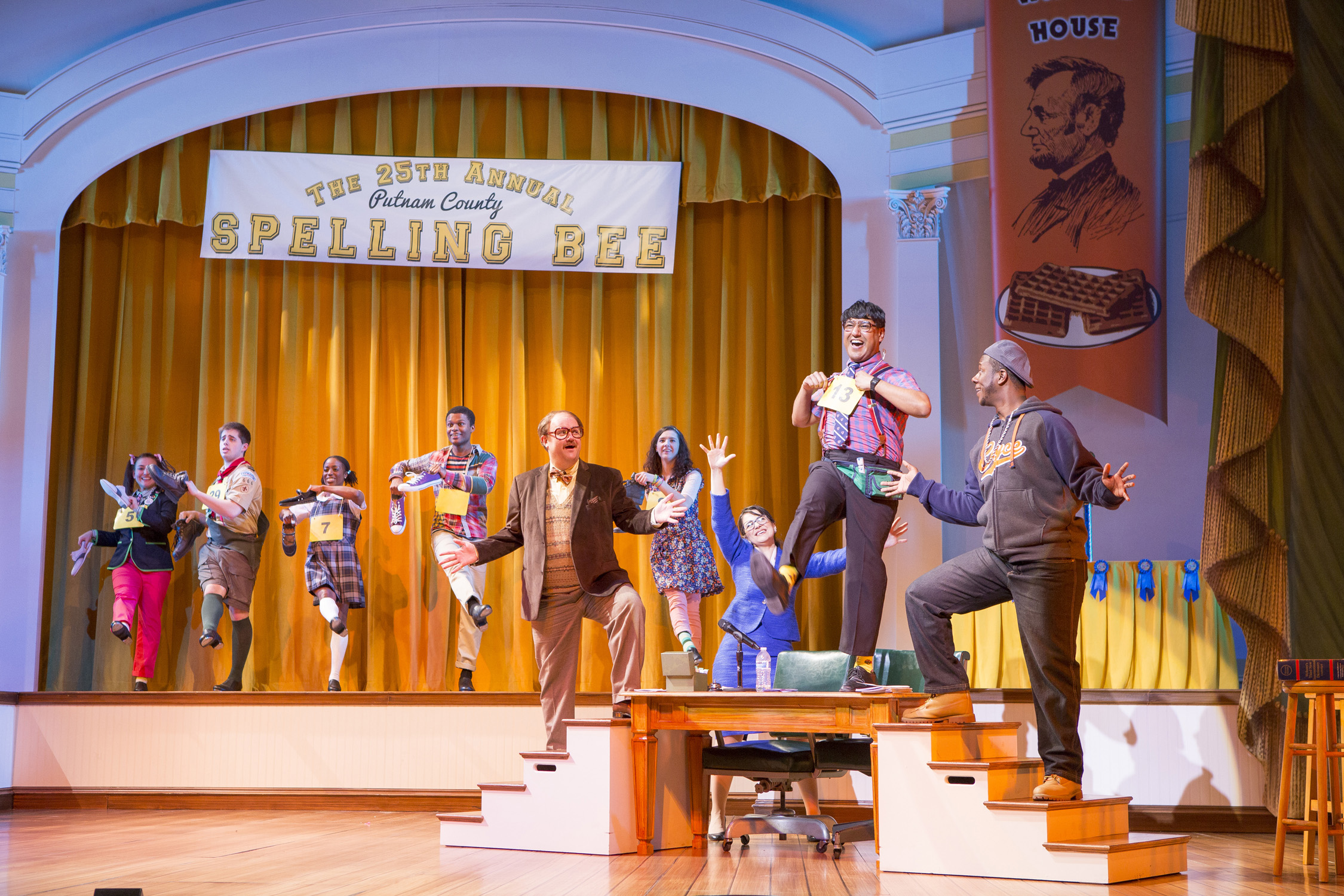 "cast of ""The 25th Annual Putnam county Spelling Bee"" stands dressed as children and teachers on the stage at For"