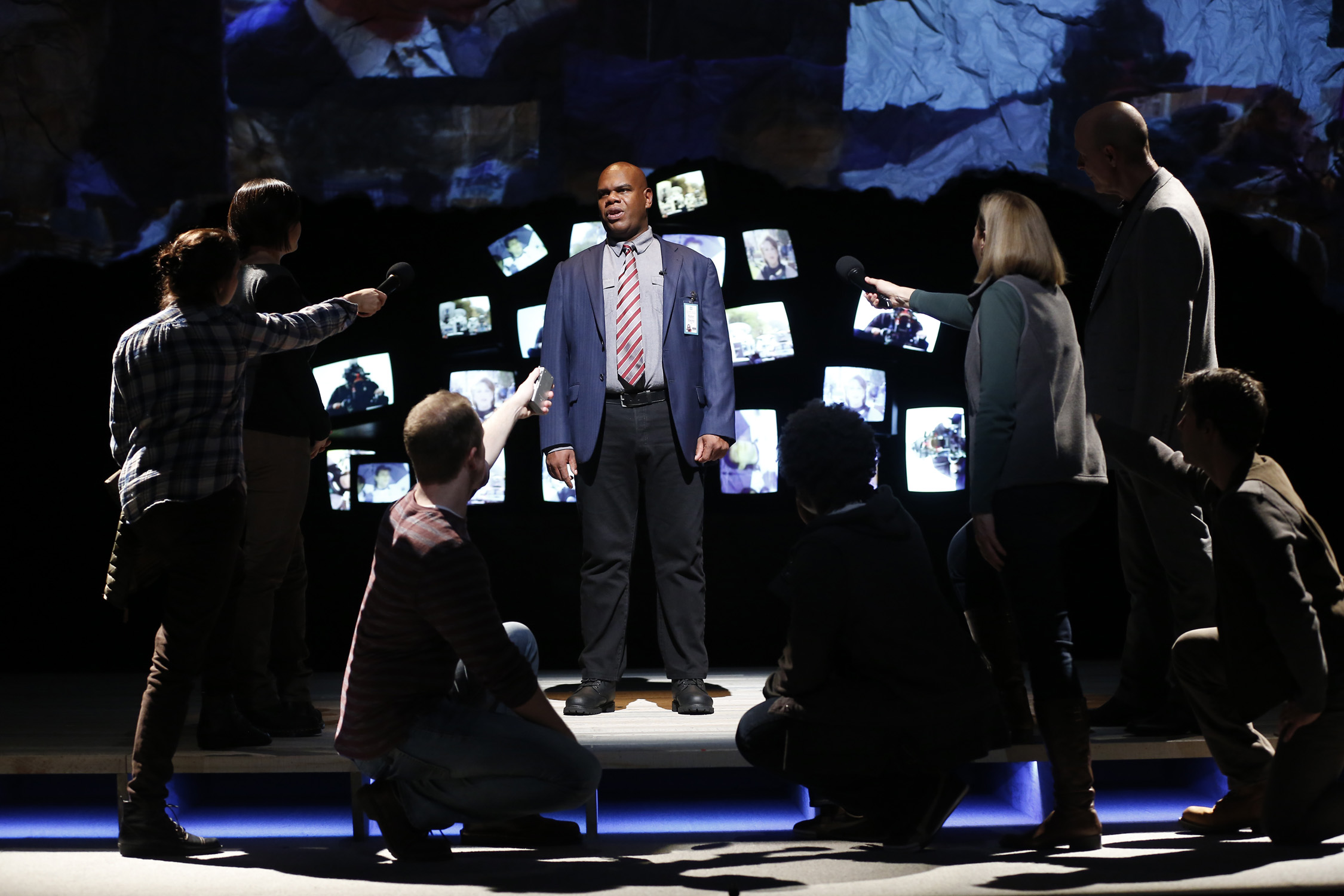 "Photo of the cast of ""The Laramie Project"" at Ford's. Set is covered in TV screens with one actor standing in the middle of the set. He is surrounded by a handfull of other actors who pose like TV reporters holding microphones and notebooks."