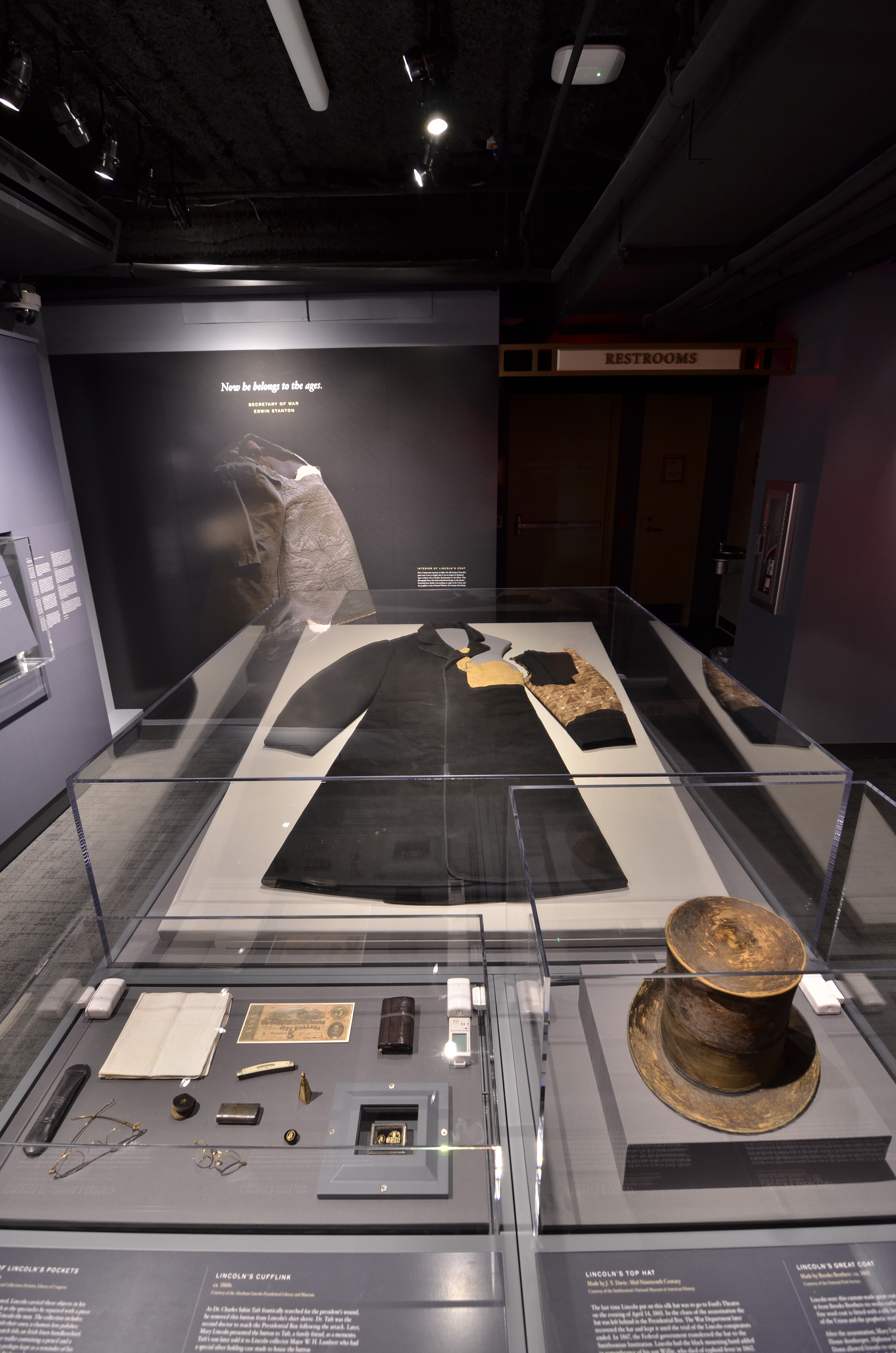 Items sit in a large, flat museum case. Pieces are Abraham Lincoln's black-wool Great Coat, his signature Top Hat, contents of his pockets including a Confederate bill, spectacles and a pocket watch,
