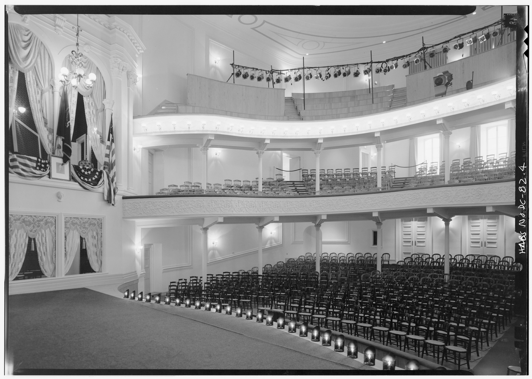 Black and white image from the Ford's Theatre stage looking out into the 1968 renovated Ford's Theatre audience. Image shows individual wooden chairs in the the audience seating areas and the Presidential Box above the stage. The Box is decorated similar to when Lincoln and his guests attended the theatre in April 1865.