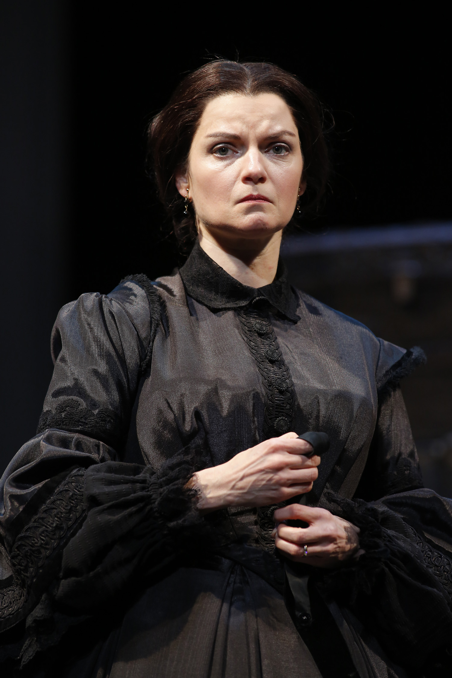 A woman dressed as Mary Lincoln wears mourning clothes and a sad expression.
