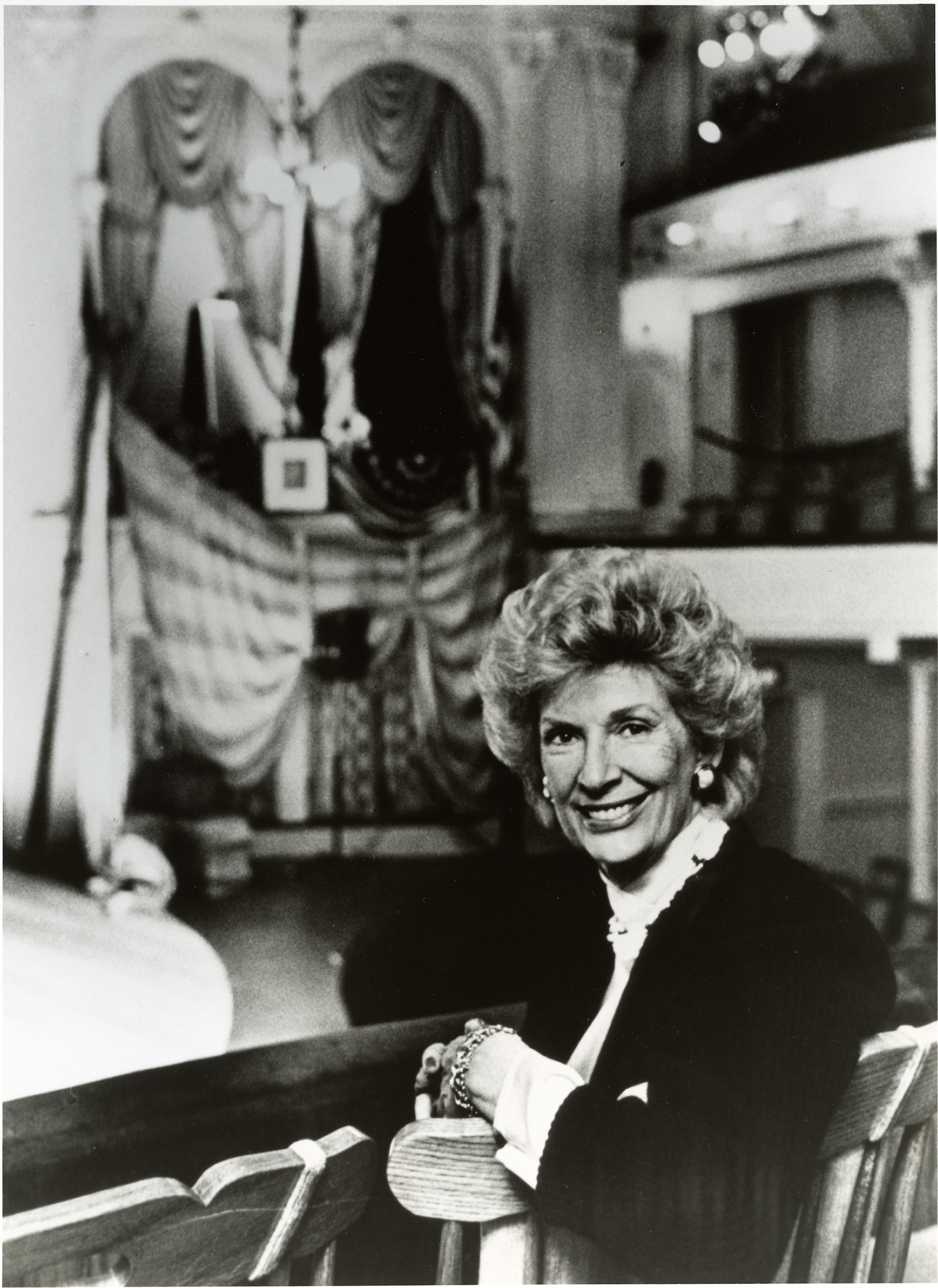 Frankie Hewitt (founder of Ford's Theatre Society) sits inside of Ford's Theatre with the Presidential Box positioned behind her. Her hair is short and permed. She wears a black tailored jacket over a white blouse with a high neck.