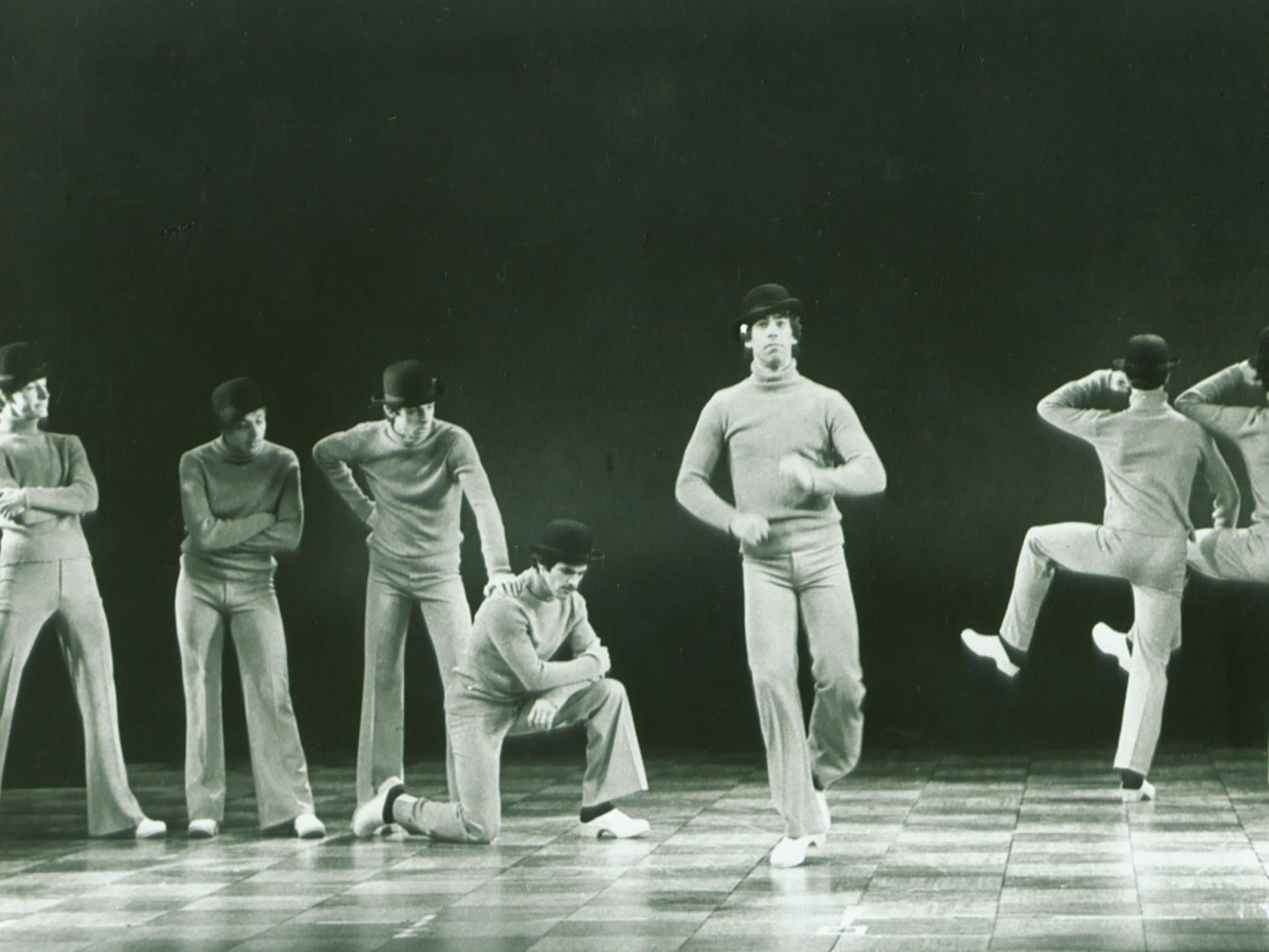eight men wearing monochrome turtlenecks and pants and black bowler hats dance on the Ford's Theatre stage.
