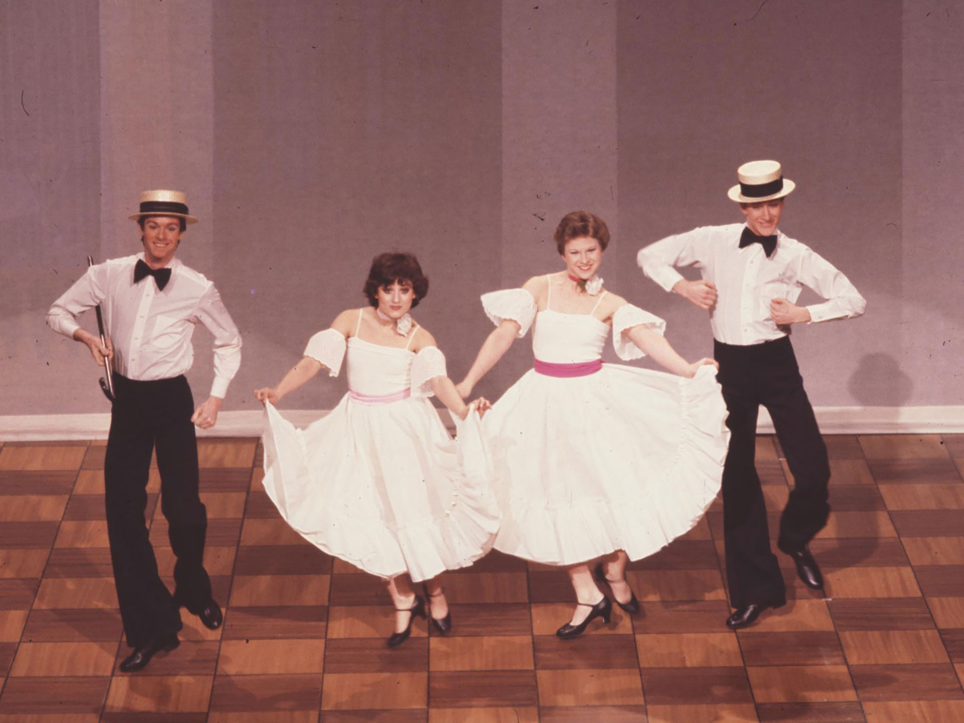 "two male dancers in 1900s straw hats, white shirts with bow-tiess and dark trousers flank two female dancers in white blouses, black-and-white vertically striped A-line skirts. The women carry parisols. All are in the Ford's production of ""American Dance Machine"""
