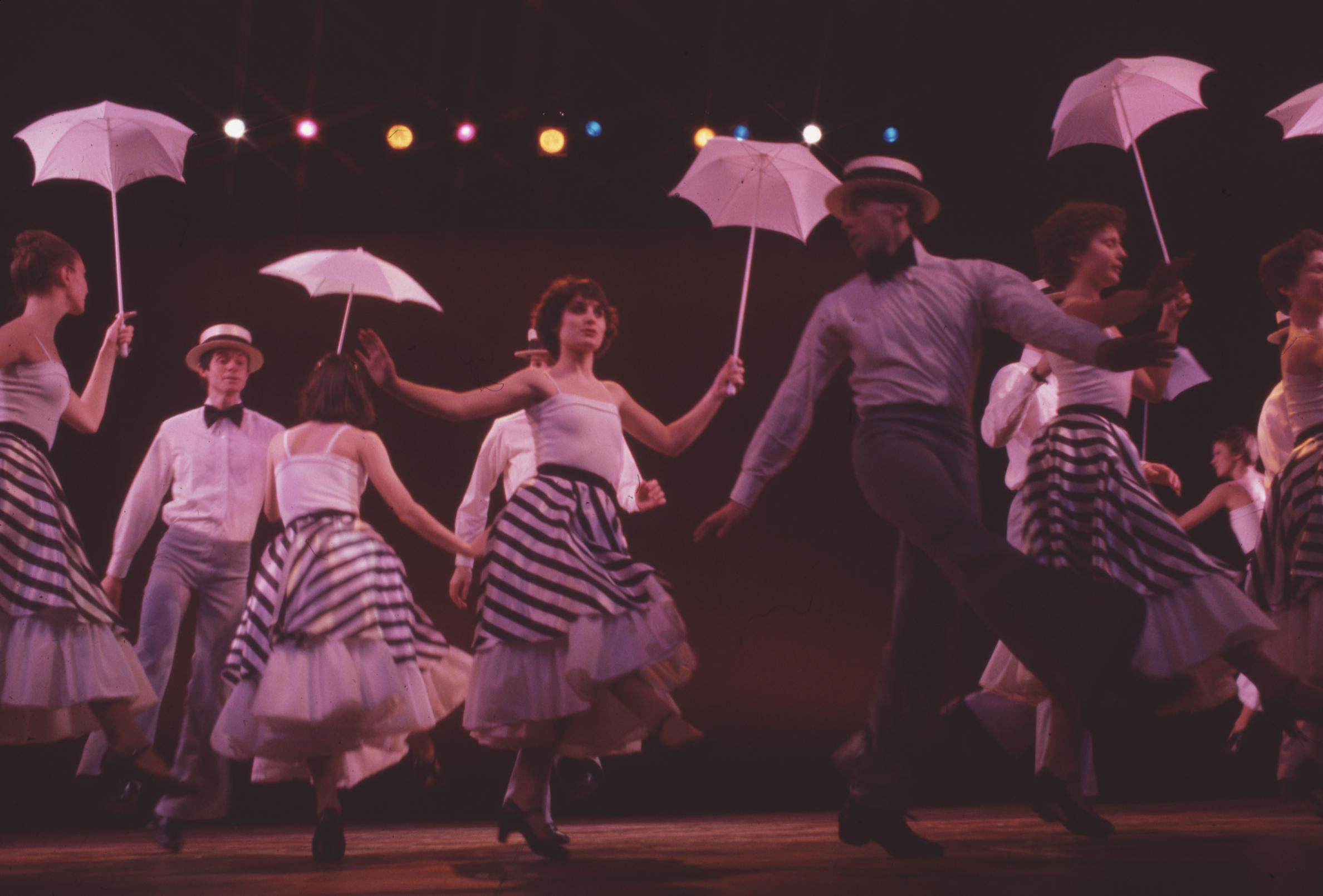 photo of seven cast members dancing in black-and-white striped pants and skirts, white blouses. The women dance with open white parisols.