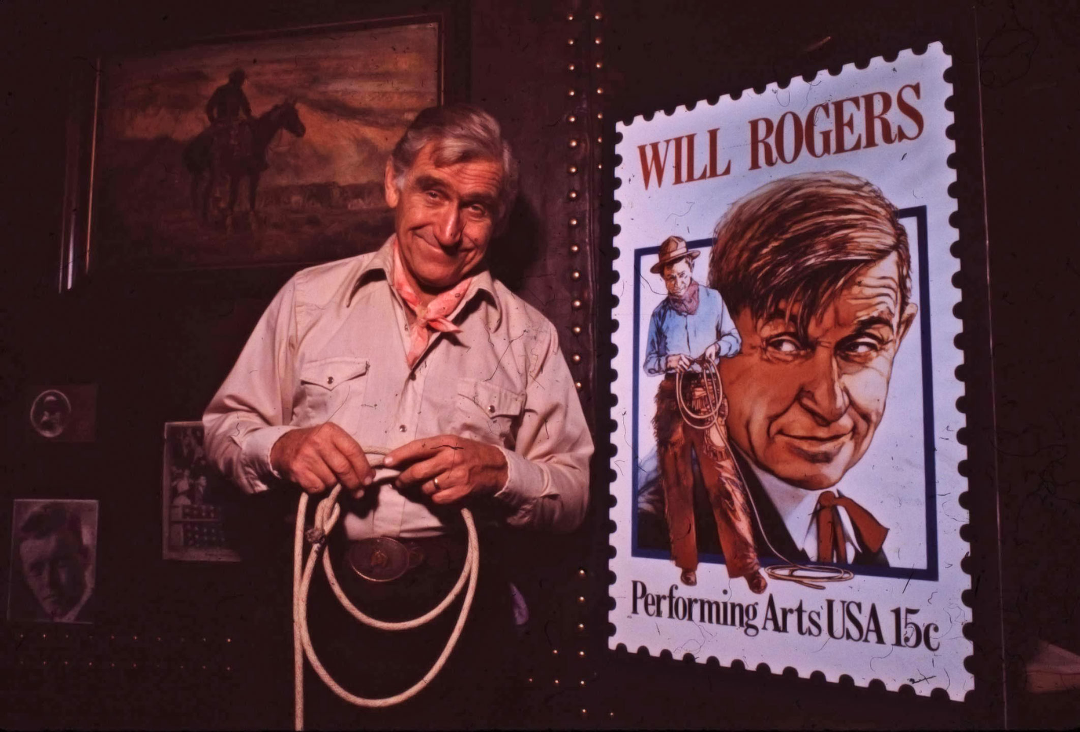 Actor James Whitmore dressed like a cowboy with a white shirt, patterned neck scarf, dark pants and large oval belt buckle. He holds a lasso. He is in character for the play Will Rogers USA, wherein he play the title role.