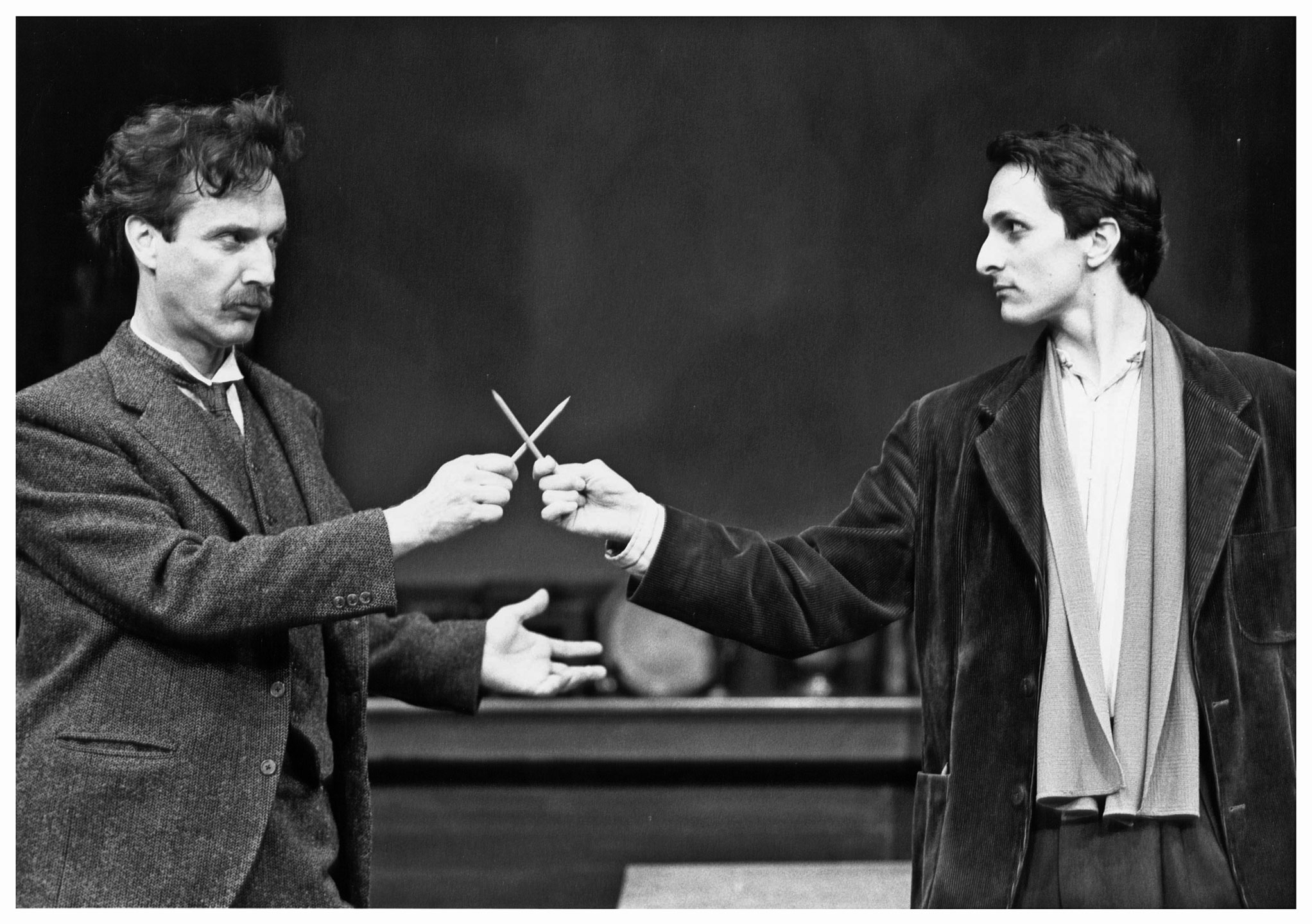 Two male actors portraying Picasso (Dan Hiatt) and Einstein (James Asher) on stage at Ford's Theatre. The two are performing in a production of the play Picasso at the Lapin Agile, my Steve Martin.
