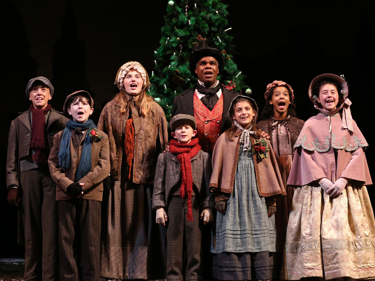 "Craig Wallace (Scrooge) and the young actor company of ""A Christmas Carol"" (2017). They stand on stage near a 2-story Christmas tree."