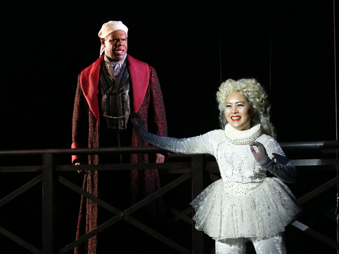 "Actors Craig Wallace (Scrooge) and Justine ""Icy"" Moral (Ghost of Christmas Past) fly high above the set in the Ford's Theatre 2017 production. He wears a long tan nightshirt, red robe and night cap. She wears a white sparking leotard, tutu and tights."