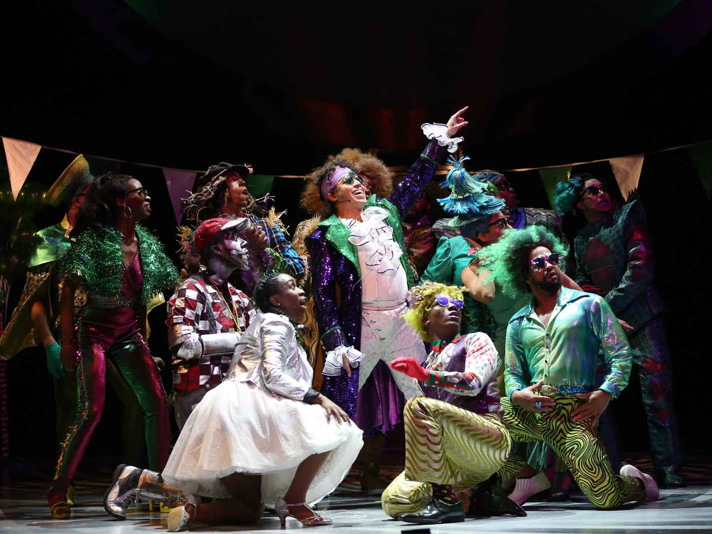 The character of The Wiz dressed in a purple velvet coat with tails, puffy-breasted white shirt and while velvet pants. He is flanked by residents of the Emerald City who are sporting green glasses and wildly patterned 1970s-styled green pants, fuzzy green jackets, curly green wigs and outlandish tiered hats in green, of course!