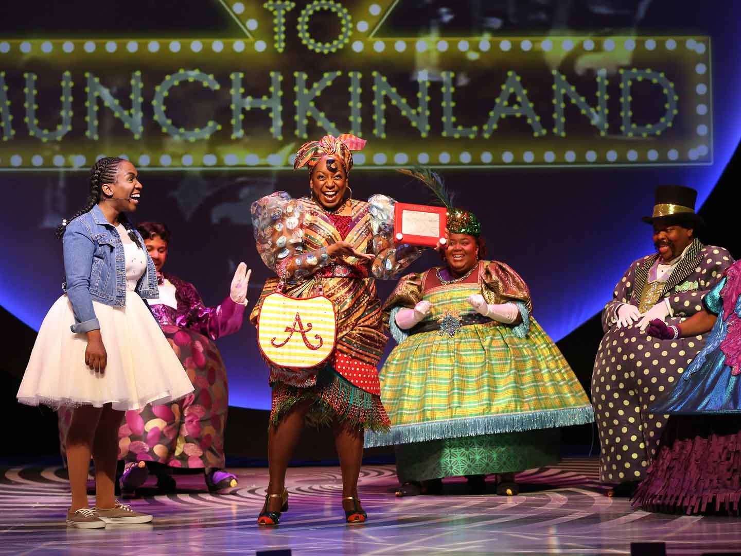 "Photo of the 2018 cast of ""The Wiz"" at Ford's Theatre. Pictured are Dorothy in a white sparkly A-line, knee-length dress and denim jacket; Addaperle holding an Etch-A-Sketch and wearing a patchwork dress of wacky patterns including clear polka-dot sleeves, an orange, green, purple and red asymmetrical striped dress with fringe at the hem and a purse with a giant Bedazzled A; and four Muchkins in brightly colored dresses and feathered hats or tuxedo jackets and top hats."