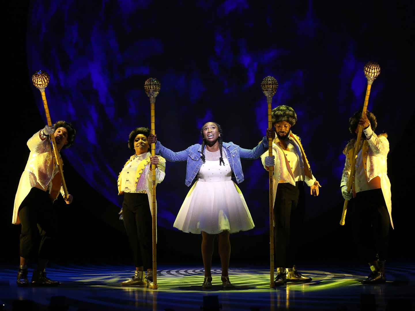 Dorothy is pictured here surrounded by the 4 actors portraying the Yellow Brick Road in The Wiz at Ford's Theatre. Dorothy wears a knee-length white dress with a long-sleeved denim jacket. Yellow Brick Road actors each have yellow-brick painted afros, sparkling buttoned band jackets with coat tails and carry septers topped with disco-balls