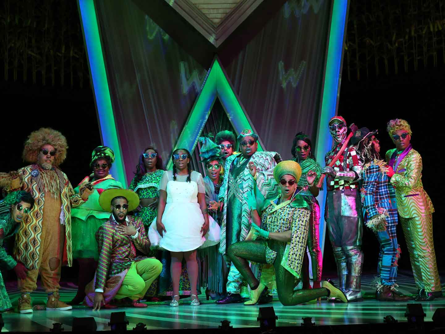 "The 2017 Ford's Theatre cast of ""The Wiz"" stands dressed in all green on stage. A large neon W is glowing behind them."