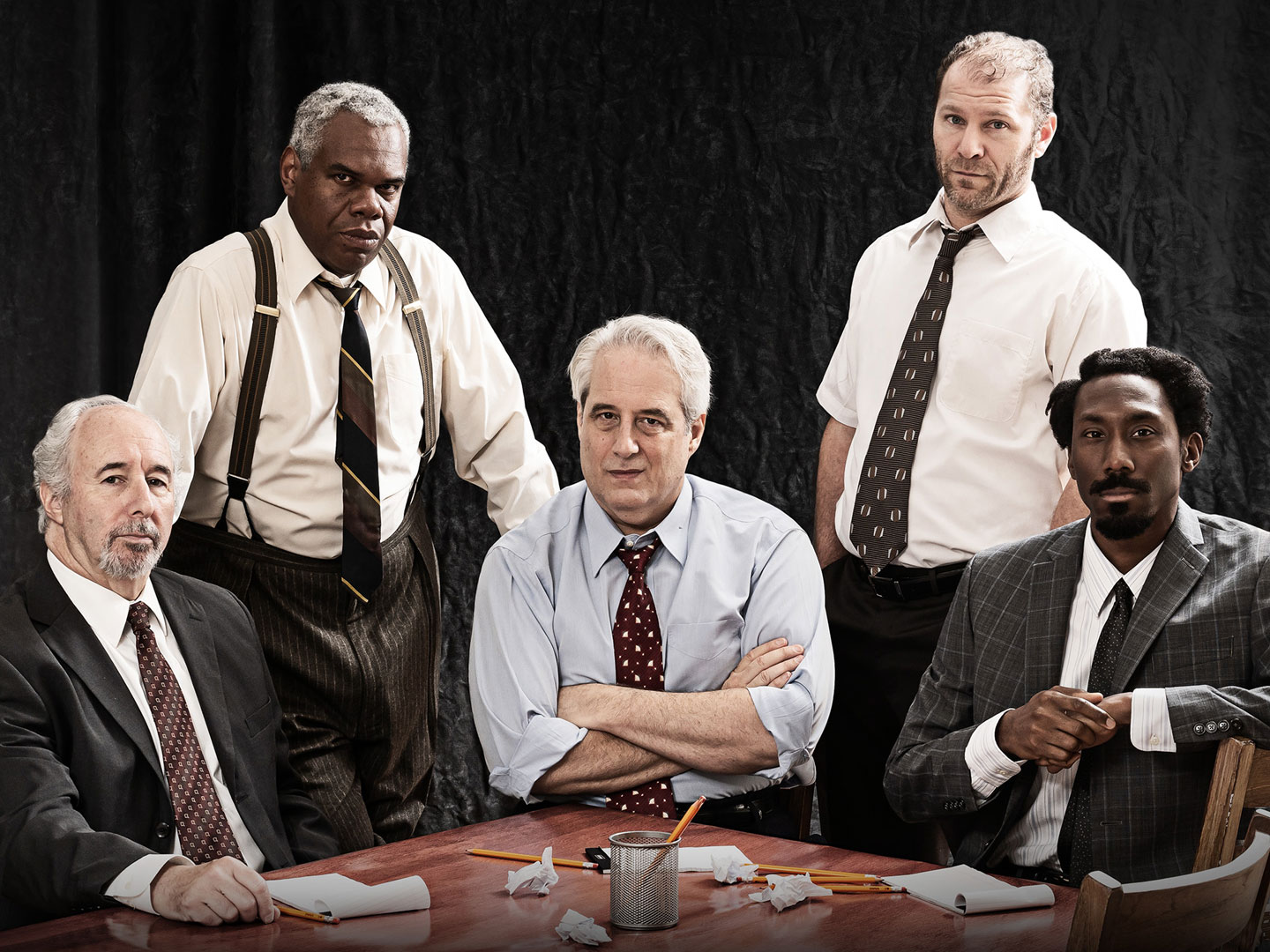 "image of 6 male actors, 3 white men and 3 black men, seated around a jury table. Image is of the cast of ""Twelve Angry Men"" at Ford's Theatre in January/February 2019. Photo by Scott Suchman."