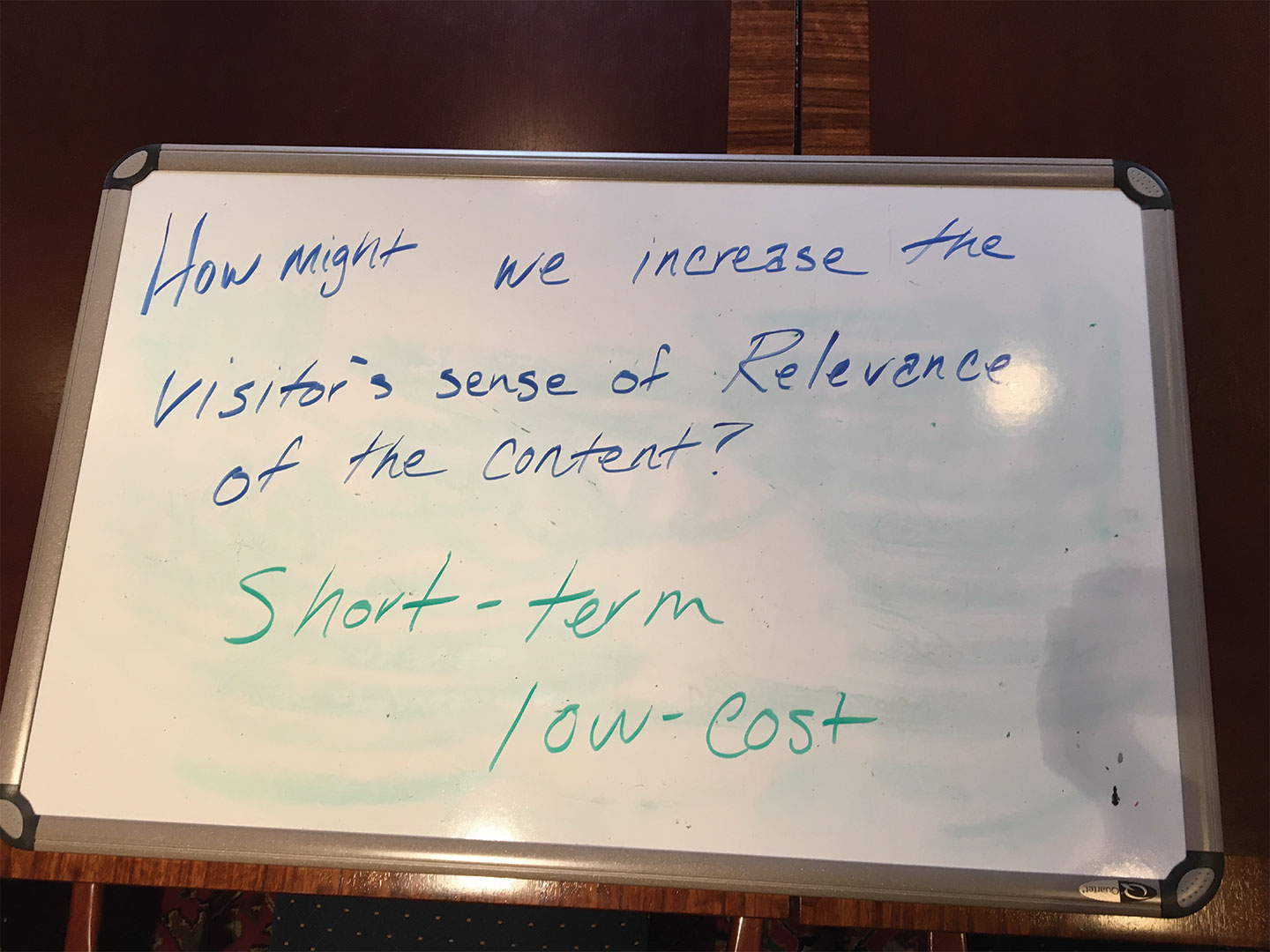 A whiteboard reads How Might We Increase the Visitor's sense of Relevance of our content; short-term; low-cost