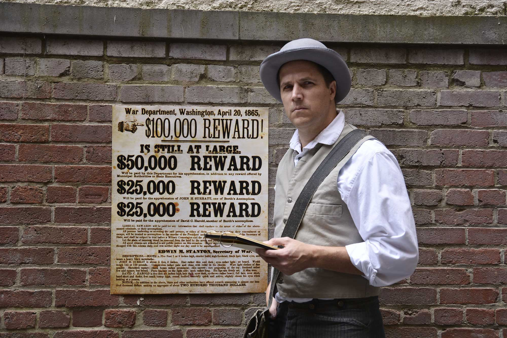 Actor Eric Messner, dressed as Detective McDevitt, stands in front of a brick wall where there is a posted wanted sign for assassin John Wilkes Booth.