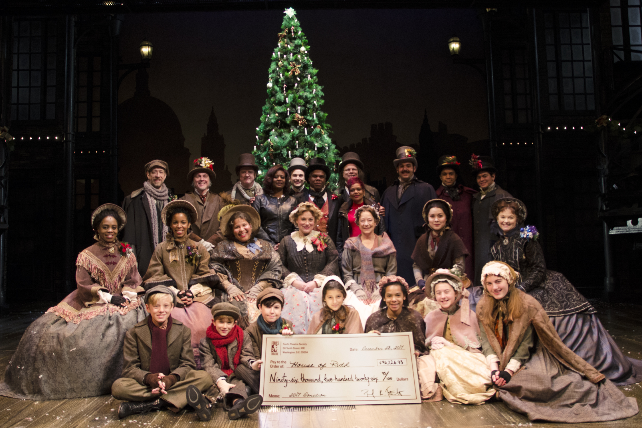 "The 2017 company of ""A Christmas Carol"" present a giant check to House of Ruth at Ford's Theatre."