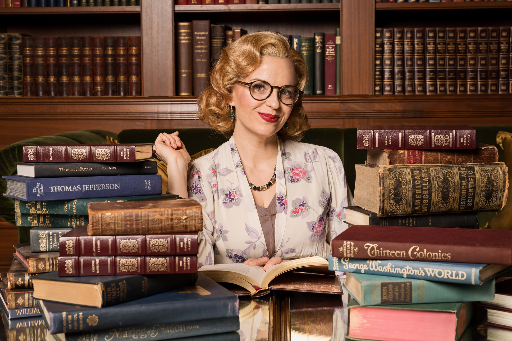 Actress Kimberly Gilbert dressed in a 1940s-stylled curled wig and creme-colored blouse sits in a library surrounded by piles of books and bookcases that are filled with books about the founding of America. Photo by Scott Suchman.