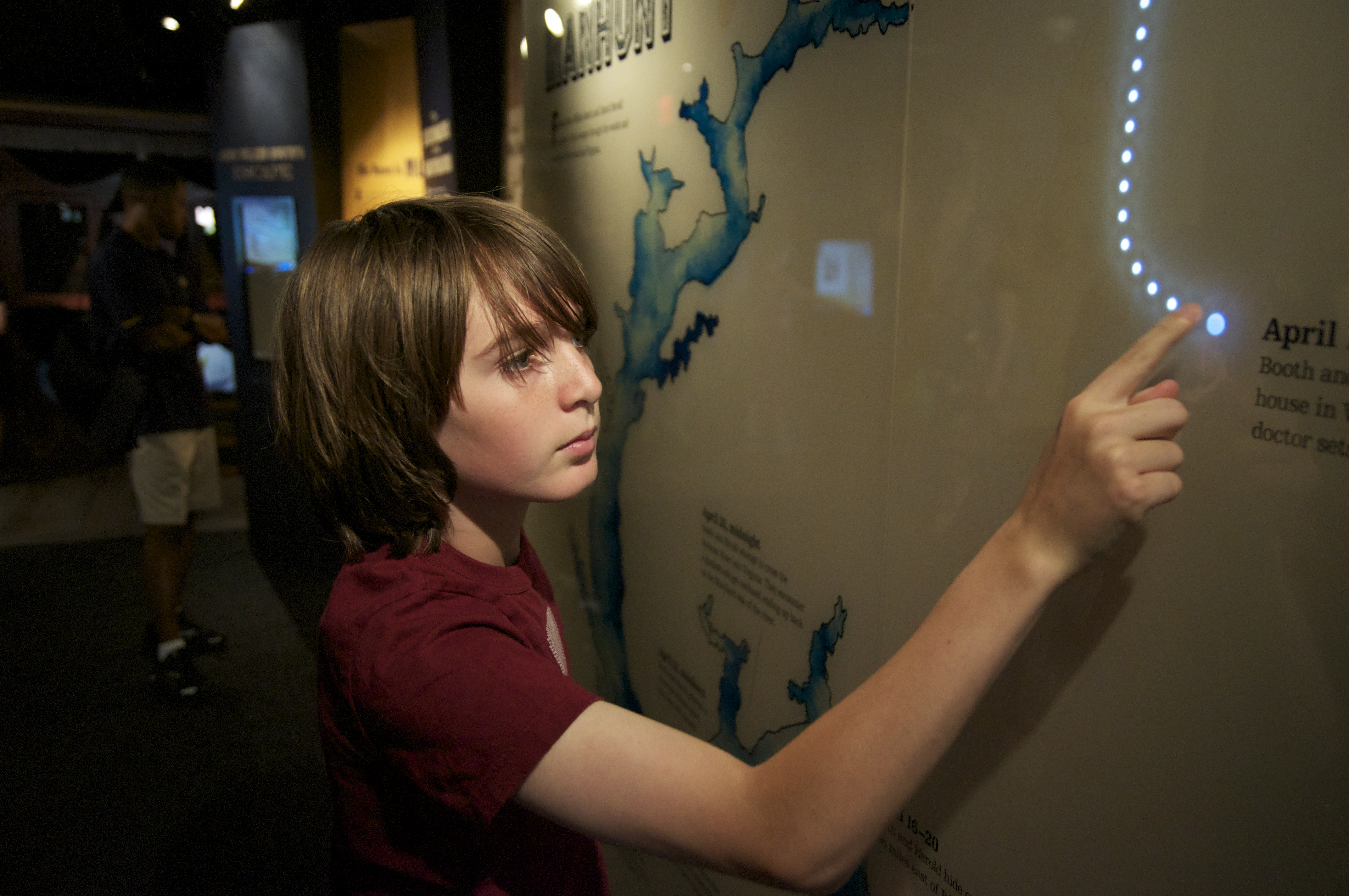An elementary-age boy with brown hair and a red short-sleeved shirt stands at a light-up map that traces the escape route of assassin John Wilkes Booth from Ford's Theatre. The map is within the exhibits at the Center for Education and Leadership.